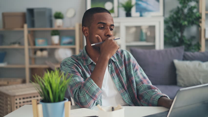 Stressed guy African American freelance worker is using laptop typing then touching head feeling tired and unhappy. Tension and stress at work and youth concept. | Shutterstock HD Video #1026193778