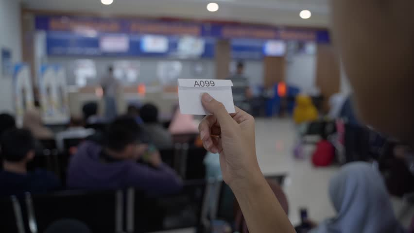 Close up of the queue number from a customers hand while waiting for a long time in public services | Shutterstock HD Video #1026201635