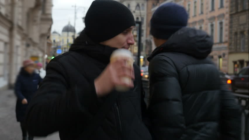 Front view  of young man walking down the city street and drinking coffee. Serious tired man in black walks on the street and bumping into people