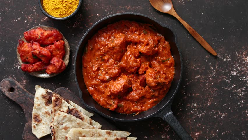 Traditional Indian chicken tikka masala spicy curry meat food in cast iron pan served with naan bread and spices. Flat lay. Top view. Royalty-Free Stock Footage #1026203885