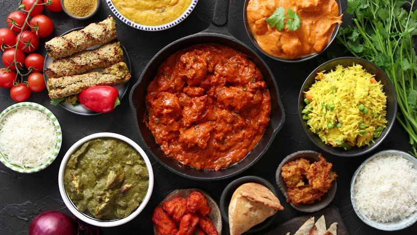 Various Indian dishes on a table. Spicy chicken Tikka Masala in iron pan. Served with rice, naan and spices. Set of different kind Indian food. Royalty-Free Stock Footage #1026203921