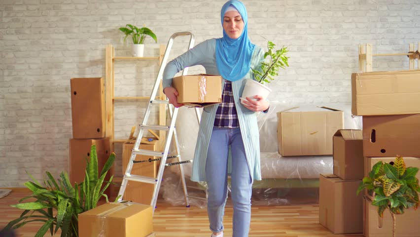 Portrait young muslim woman in a hijab with a flower and a box in her hands   Shutterstock HD Video #1026227393