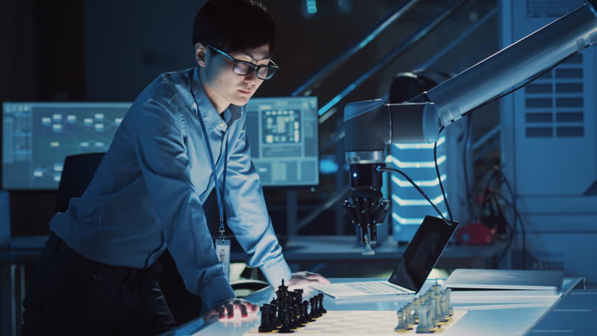Professional Japanese Development Engineer is Testing an Artificial Intelligence Interface by Playing Chess with a Futuristic Robotic Arm. They are in a High Tech Modern Research Laboratory. #1026241850