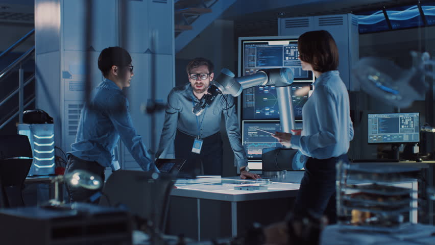 Diverse Team of Engineers with Laptop and a Tablet Analyse and Discuss How a Futuristic Robotic Arm Works and Moves a Metal Object. They are in a High Tech Research Laboratory with Modern Equipment. Royalty-Free Stock Footage #1026241940