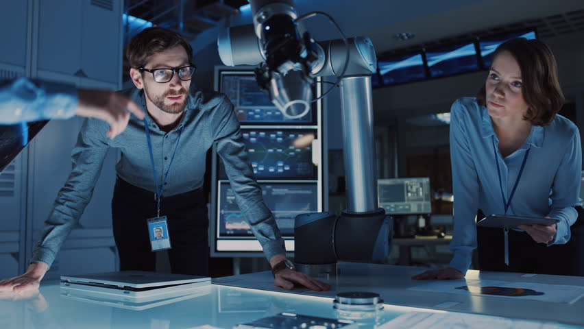 Diverse Team of Engineers with Laptop and a Tablet Analyse and Discuss How a Futuristic Robotic Arm Works and Moves a Metal Object. They are in a High Tech Research Laboratory with Modern Equipment. #1026241952