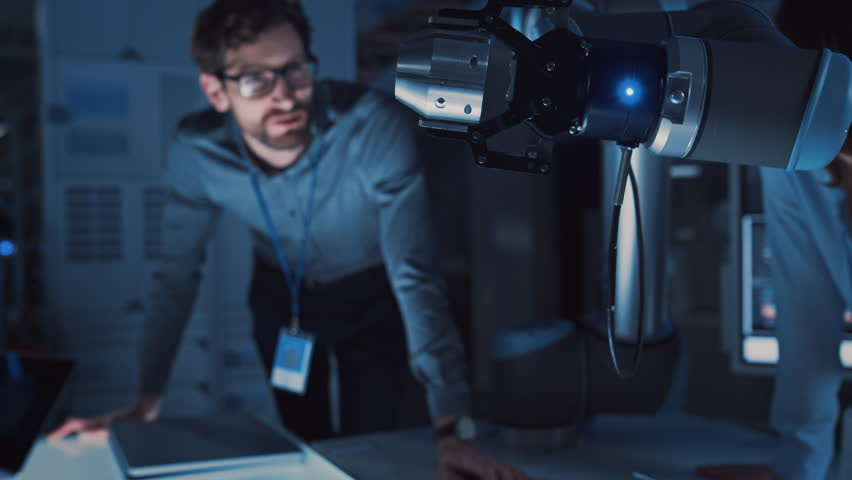 Close Up of a Futuristic Robotic Arm Moving a Metal Object and Placing It. Team of Engineers Following This Advanced Process. They are in a High Tech Research Laboratory with Modern Equipment. | Shutterstock HD Video #1026242003