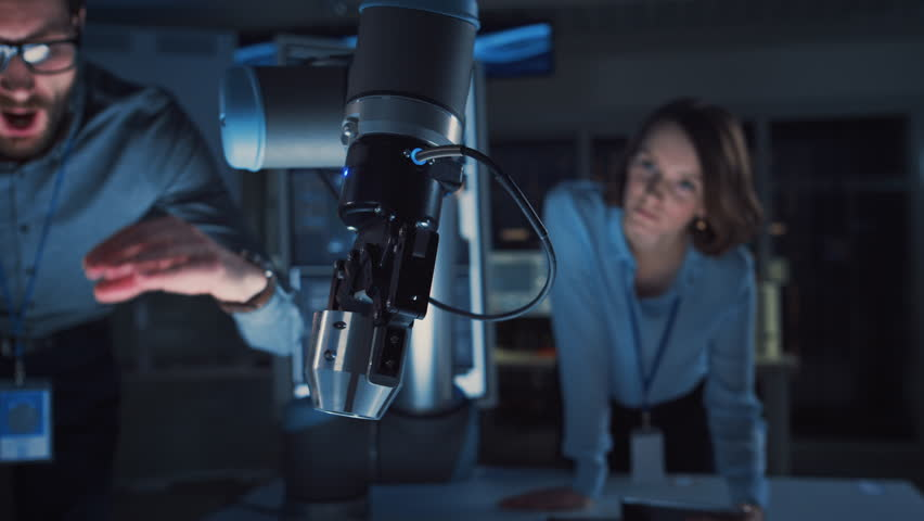 Close Up of a Futuristic Robotic Arm Picking Up a Metal Object and Moving It. Team of Engineers Following This Advanced Process. They are in a High Tech Research Laboratory with Modern Equipment. #1026242006