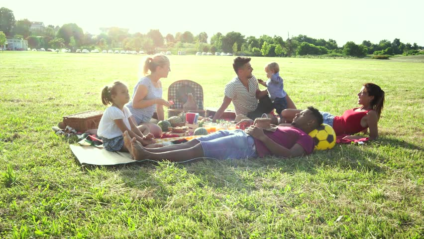 Happy multiracial families having fun together with kids at pic nic party outdoors - Multiethnic joy and love concept with mixed race people playing with children at park - Warm backlight color tones #1026250259