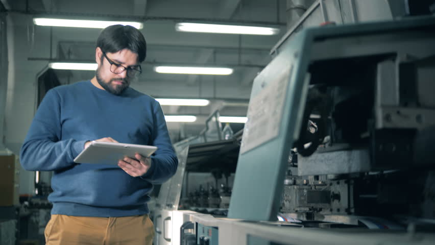 Man with a tablet computer is inspecting a functioning printing equipment #1026251090