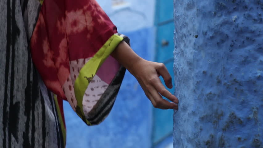 Women walking through the beautiful village Chefchaouen in Morocco, draging her hand across the typical blue walls.