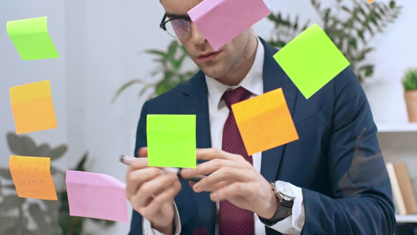 Handsome, attentive businessman writing on sticky notes | Shutterstock HD Video #1026266276