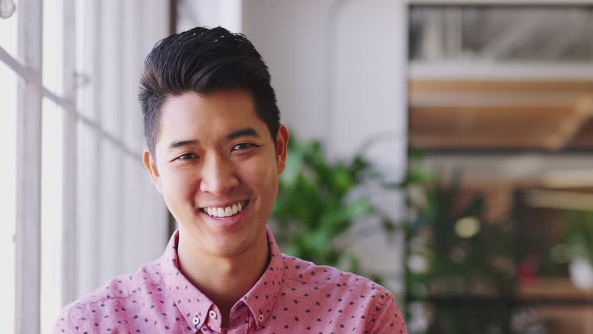 Millennial Asian male creative standing in an office turning and smiling to camera, close up #1026274511