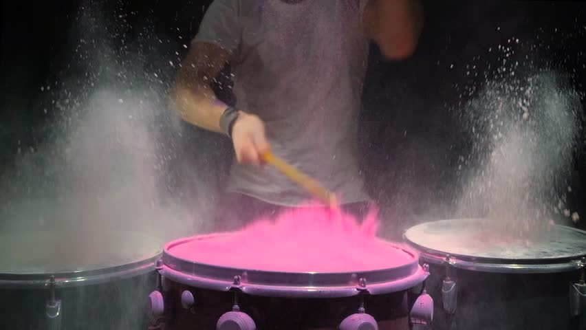 Red holi powder bounces off drum in shockwave pattern, slow motion. black background. | Shutterstock HD Video #1026281756