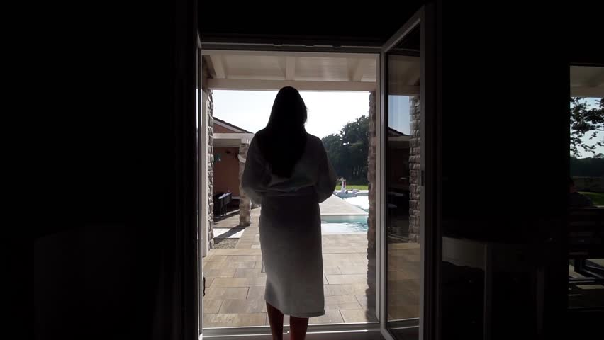 Beautiful woman walks to villa pool, calling you to join before throwing robe wide to enter pool