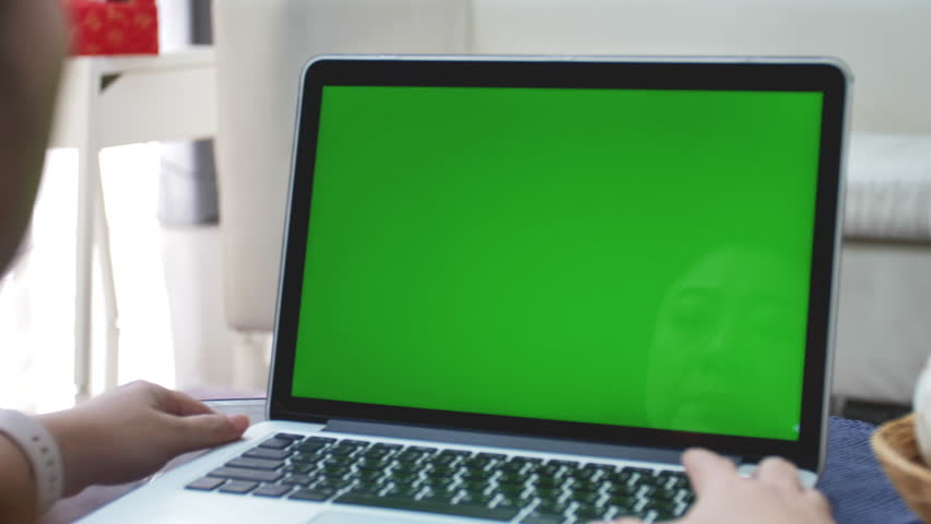 Over the shoulder shot of Asian woman looking at green screen. Office person using laptop computer with laptop green screen, 4K dolly shot