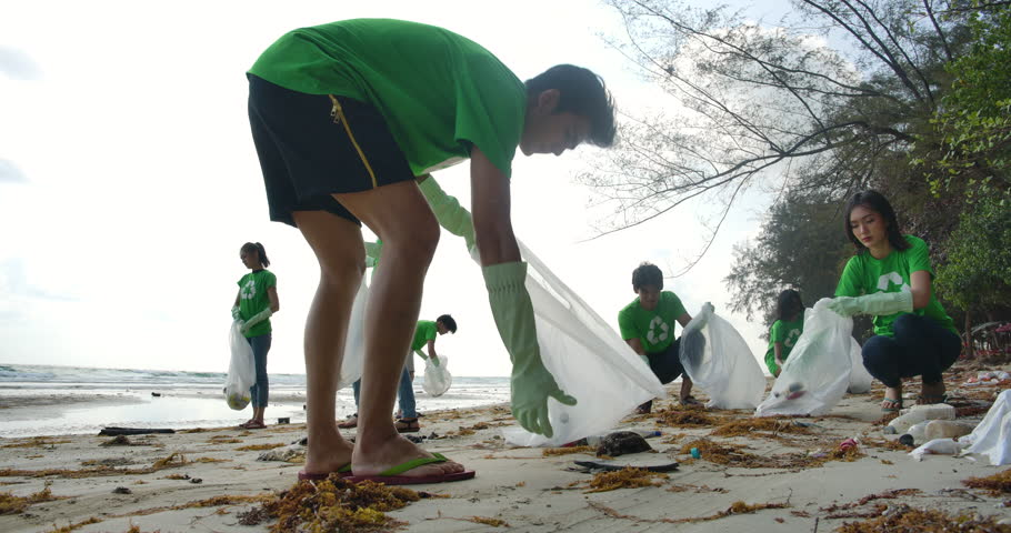 Group of young asian people volunteers in green t-shirts cleaning up the beach with plastic bags full of garbage. Safe ecology concept. 4k resolution. | Shutterstock HD Video #1026301061