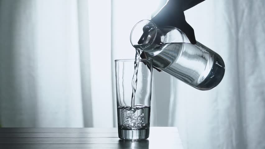 Woman's hand pouring fresh pure water from bottle into a glass on the table, health and diet concept, Slow motion footage | Shutterstock HD Video #1026303155