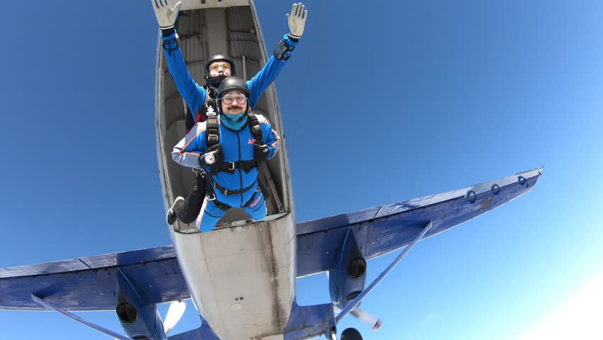 Tandem skydiving. Two guys are flying in the sky. | Shutterstock HD Video #1026308432