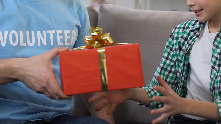 Volunteer presenting giftbox to little boy from low-income family, state support