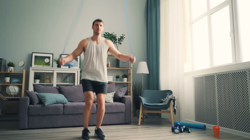 Good-looking sportsman is jumping rope training at home alone wearing sportswear and sneakers enjoying physical activity. People, sports and interior concept.