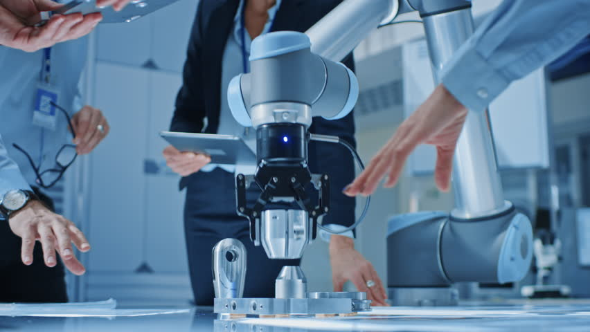 Team of Industrial Robotics Engineers Gathered Around Table With Robot Arm, They Use Tablet Computer to Manipulate and Program it to Pick Up and Move Metal Component. Focus on Hands | Shutterstock HD Video #1026344528