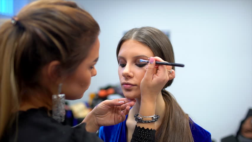 fashion show, visagist working, making professional make up, backstage. beautiful face of female girl model. Make up artist applying stylish makeup to young woman, visage for beauty contest 4 K