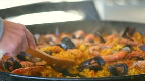 Paella traditional Spanish food. Person putts seafood paella from the fry pan to plate. Paella with with mussels, king prawns, langoustine and squids. Person cooking paella. Dinner. Slow motion 4K