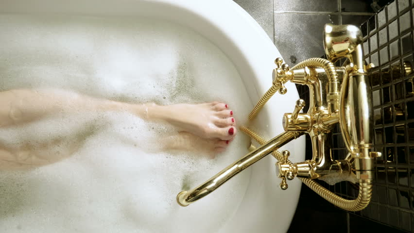 Top view of water flowing from golden faucet into the bathtub. The slim legs and feet with red pedicure of young woman taking a bubble bath. 4K