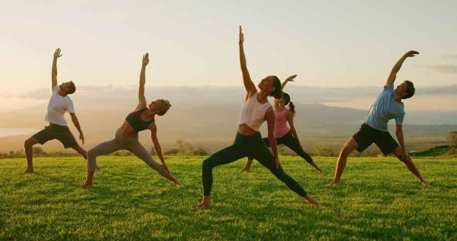 Yoga class at sunset, happy diverse group of young people practicing yoga poses together, stretching health and wellness