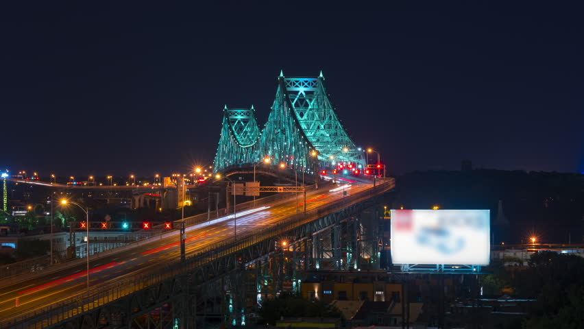 Big city traffic travelling over the Jacques Cartier bridge in Montreal Quebec at night. Long exposure light trails show a fast paced city.