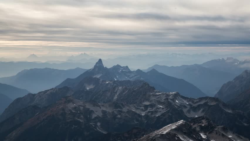 Aerial view of the rugged Canadian landscape of the mountain peaks covered in clouds. Taken near Chilliwack, East of Vancouver, British Columbia, Canada, during a cloudy evening. Continuous Animation   Shutterstock HD Video #1026381713