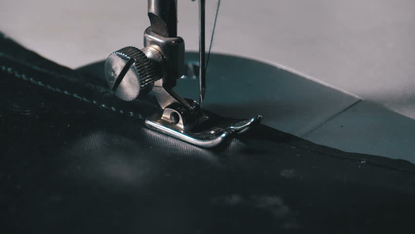 Sewing Machine Needle in Motion. Close-up of sewing machine needle rapidly moves up and down. The tailor sews black fabric on the sewing workshop. The process of sewing fabric. | Shutterstock HD Video #1026404897