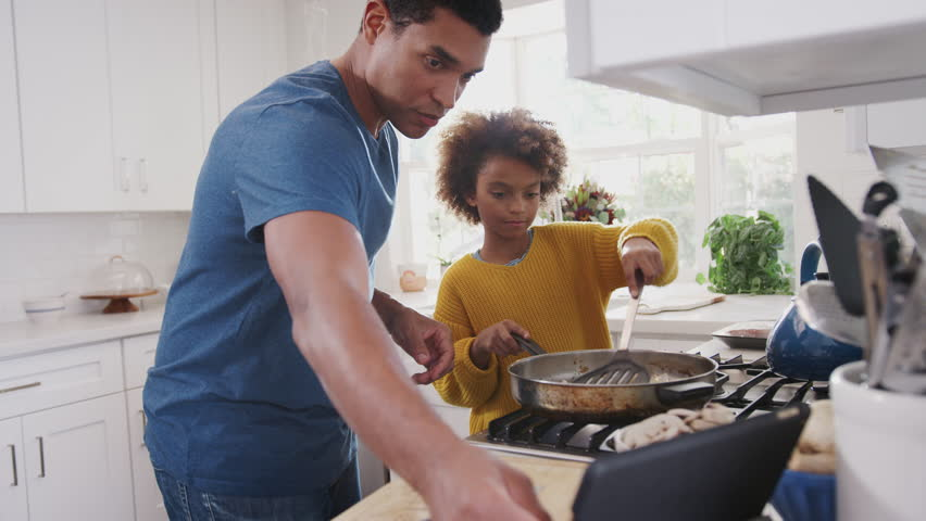 Pre-teen black girl and her father preparing food following a recipe on a tablet computer, close up
