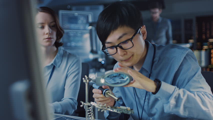 Japanese Development Engineer in Blue Shirt is Soldering a Circuit Board in a High Tech Research Laboratory with Modern Equipment. His Colleague Asks Him a Questio and Points on the Compter Screen.