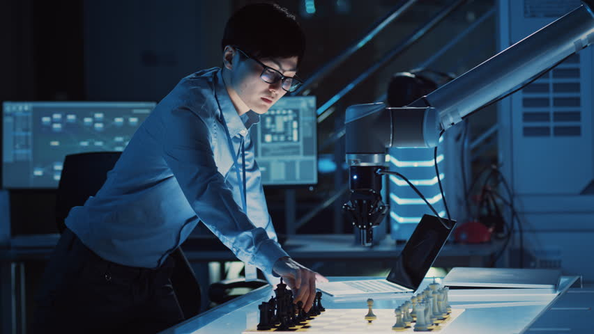 Professional Japanese Development Engineer is Testing an Artificial Intelligence Interface by Playing Chess with a Futuristic Robotic Arm. They are in a High Tech Modern Research Laboratory. #1026410213