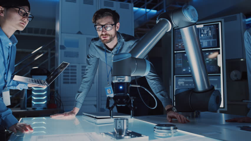 Diverse Team of Engineers with Laptop and a Tablet Analyse and Discuss How a Futuristic Robotic Arm Works and Moves a Metal Object. They are in a High Tech Research Laboratory with Modern Equipment. Royalty-Free Stock Footage #1026410222
