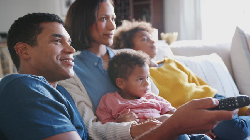Young family sitting together on the sofa in their living room watching TV, close up, side view