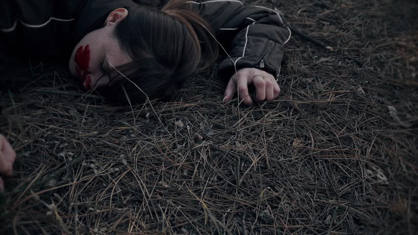 Murdered young woman lying on ground with mobile phone and axe in woods | Shutterstock HD Video #1026414170