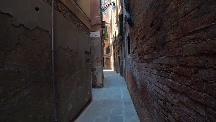 4K. Walking through of a narrow street in Venice, Italy. Subjective shot of a person who is walking on an old way. Royalty-Free Stock Footage #1026424097