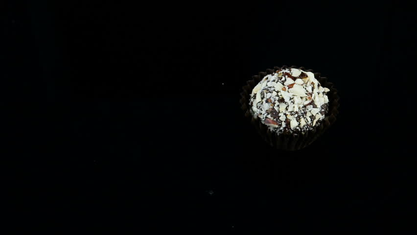 Smooth panorama down on single chocolate candy decorated with crushed nuts served on black background | Shutterstock HD Video #1026429551