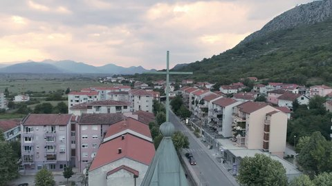 Drone footage of the top of the local catholic church in Ljubuski, Bosnia and Herzegovina. Beautiful mountains and colourful cloudy sky during sunset in the background.