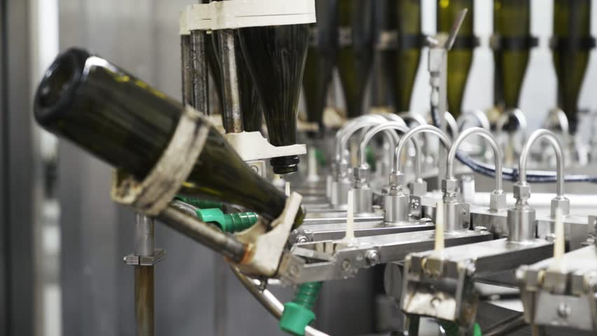 Slow-motion, glass bottles on the automatic conveyor line at the champagne or wine factory. Plant for bottling alcoholic beverages | Shutterstock HD Video #1026448316