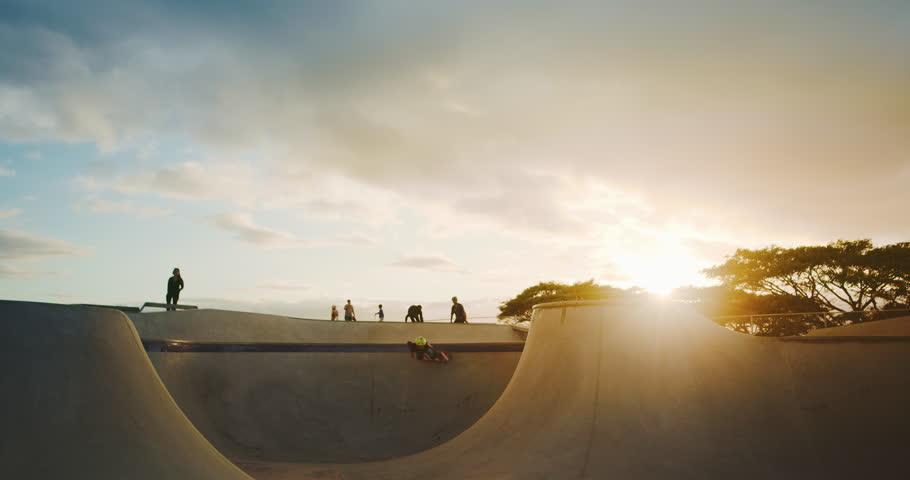 Skateboarder kid flying through the air in skate park at sunset, extreme skateboarding kid jumping high, young skateboarding shredder in slow motion