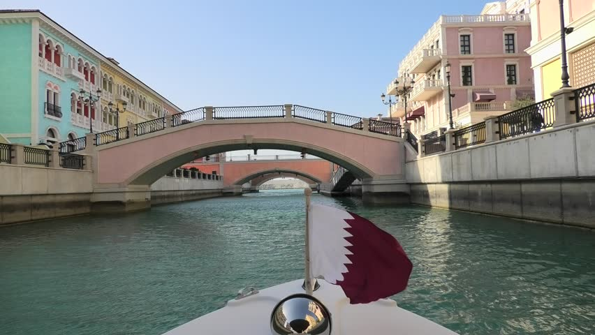 Venetian bridge on canals of picturesque Qanat Quartier icon of Doha, Qatar from a touristic boat with flag of Qatar. Venice at the Pearl, Persian Gulf, Middle East. Famous attraction at sunset light. | Shutterstock HD Video #1026458162