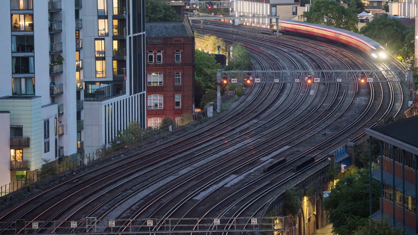 Time-lapse of trains in London UK zooming smoothly across mutliple tracks.