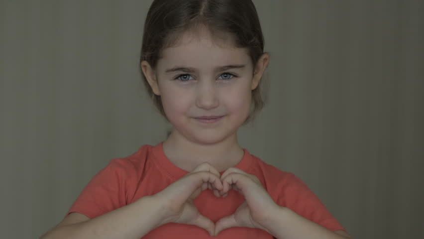 Cute little girl making a heart with her hands and smiling. Young beautiful girl smiling in love showing heart symbol and shape with hands. Romantic concept. Mothers Day.  | Shutterstock HD Video #1026471269