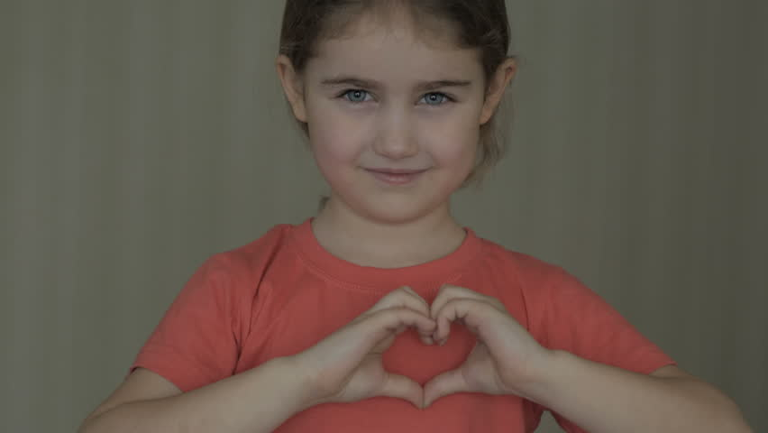 Cute little girl making a heart with her hands and smiling. Young beautiful girl smiling in love showing heart symbol and shape with hands. Romantic concept. Mothers Day.  | Shutterstock HD Video #1026471272