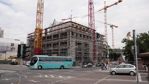 Frankfurt, Germany. June 2014. Building under construction with traffic and people on intersection. Time lapse.