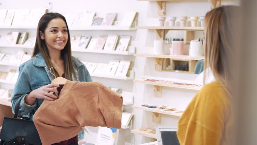 Customer Paying For Clothes At Sales Desk With Credit Card In Fashion Store