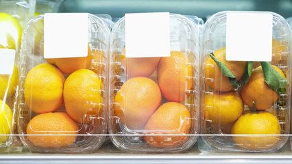 Footage of plastic containers with ripe orange fruits in food aisle at supermarket.Buy natural fruit for healthy nutrition.Video of oranges and mandarins packed in transparent boxes in foods market